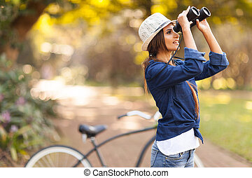 young woman bird watching at the park - attractive young...