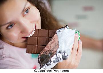 young woman bites a chocolate bar. Close-up