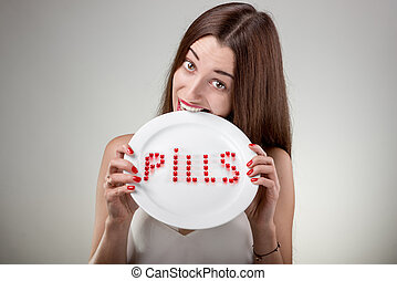 Young woman bites plate with pills