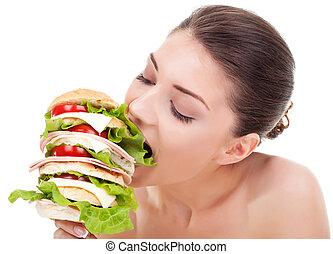 young woman biting a big sandwich