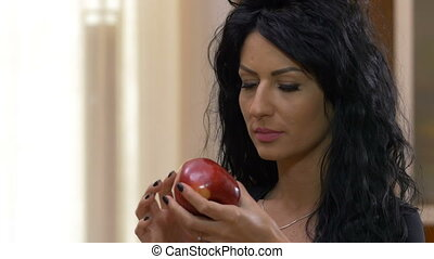 Young woman biting and eating a tasty red apple