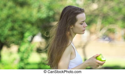 Young woman biting and eating tasty green apple
