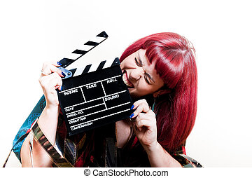Young woman biting movie clapper board