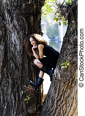 Young Woman Black Dress Sitting Between Tree Trunks