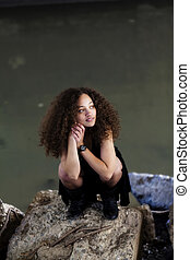 Young Woman Black Dress Squatting On Concrete Blocks