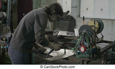 Young woman blacksmith wearing casual clothes cutting...