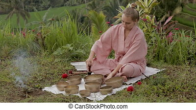 Young woman blonde in a pink kimono plays on a singing bowl. View from above. Sound meditation, healing. Rice terraces Jatiluwih in the background. High quality 4k footage