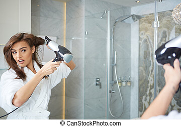 Young woman blow drying hair
