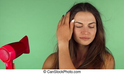 Young woman blow drying her hair on chromakey background -...