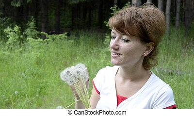 Young woman blowing a dandelion