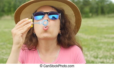 Young woman blowing bubbles outdoors