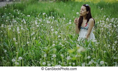 Young Woman Blowing Dandelion and Laughing
