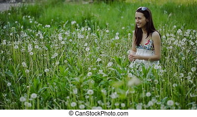 Young Woman Blowing Dandelion on a Summer Field