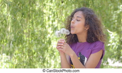 Young woman blowing dandelion seeds