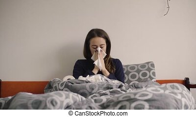 Young woman blowing nose in paper tissue in the bed