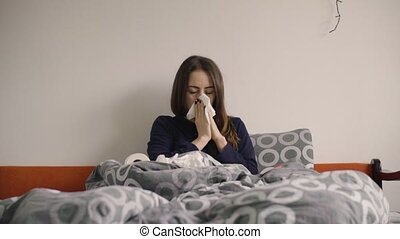 Young woman blowing nose in the bed.
