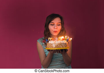 Young woman blowing out candles on a birthday cake over red background.