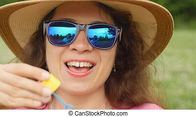 Young woman blowing soap bubbles in a park