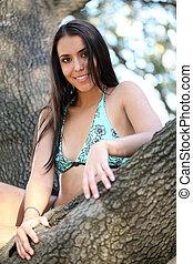 Young woman blue bikini in oak tree