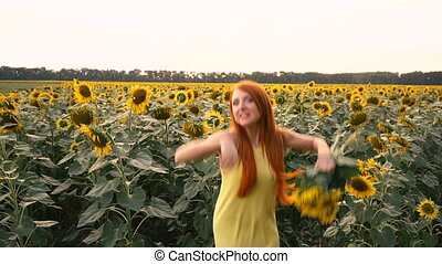 Young woman bobbing up in field of sunflowers, slow motion