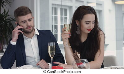 young woman bored to date while her boyfriend having business cell on mobile phone,man busy using their smart phones at the restaurant