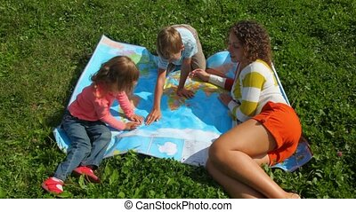 young woman, boy and little girl sitting on green grass, looks at political map