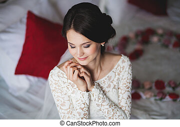 Young woman, bride in hotel sitting on bed