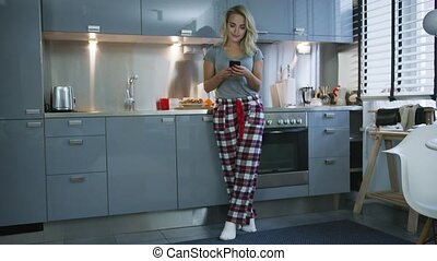 Young woman browsing smartphone in kitchen - Lovely young...