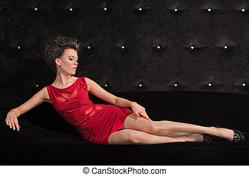 Young woman brunette in red dress laying on black sofa
