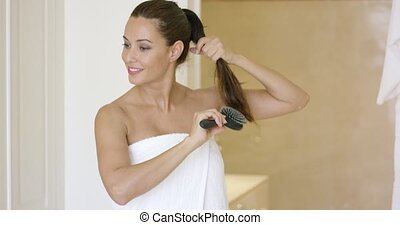Young woman brushing her long hair - Young woman brushing...