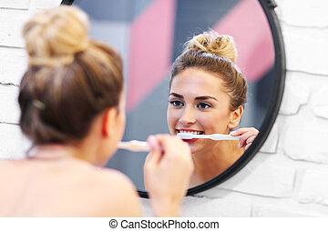 Young woman brushing teeth in bathroom