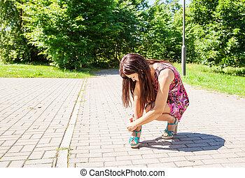 woman buttoning shoe on the sidewalk
