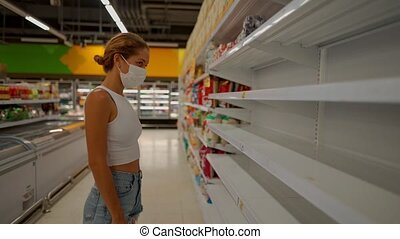 young woman wearing protect mask in shop with empty shelves