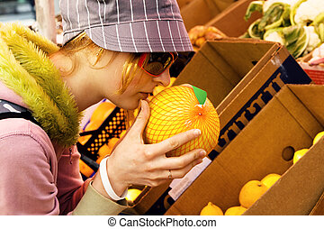 Young woman buying a melon