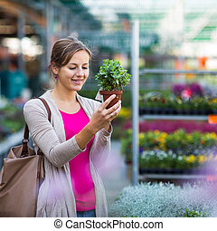 Young woman buying flowers at a garden center (color toned...