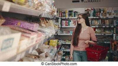 Charming lady with dark long hair holding red basket while walking between rows at supermarket. Young woman in eyeglasses buying fresh food at grocery store.