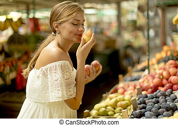 Young woman buying fruits on the market