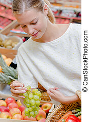 Young woman buying grapes