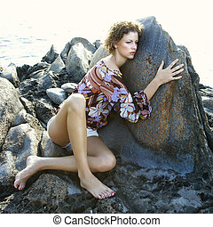 Young woman by rock. - Pensive young adult women clinging to...