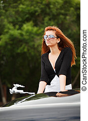 Young woman by the classic car