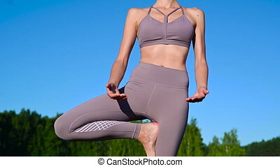 Young woman by the lake practicing yoga moves on wooden platform. Pretty young woman exercising in nature, healthy lifestyle young people positive vibes
