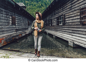 Young woman by the wooden house