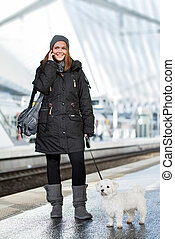 young woman calling at train station with maltese dog on the line
