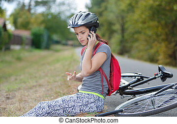 young woman calling for help after falling down from bicycle