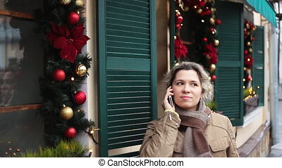 Young woman calling mobile in front of Christmas decor