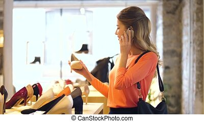 young woman calling on smartphone at shoestore