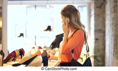 young woman calling on smartphone at shoestore - sale,...