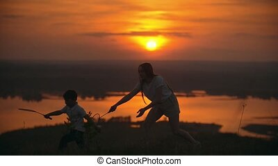 Young woman calling the child to play badminton on the hill...