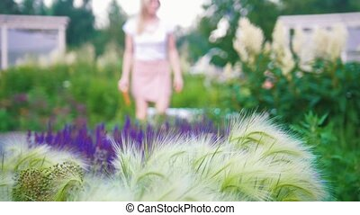 Young woman came to the garden around beautiful flowers sitting down to read a book, blurred