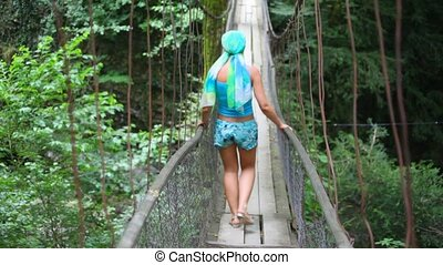 young woman carefully going on suspension bridge in forest